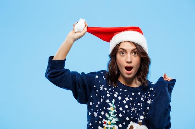 Joven sorprendió a hermosa chica morena en suéter de punto y sombrero de navidad sobre pared azul
