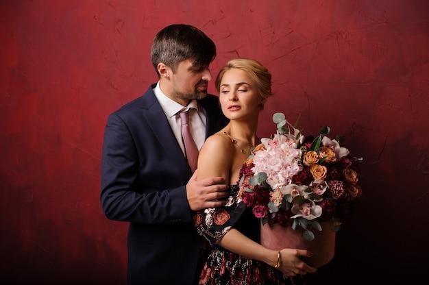 Joven sostenga a su mujer en el hombro con el ramo de flores