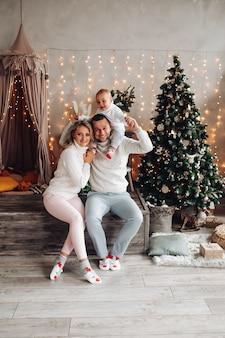 Joven sosteniendo al niño sobre sus hombros mientras está sentado al lado de su bella esposa en una habitación decorada