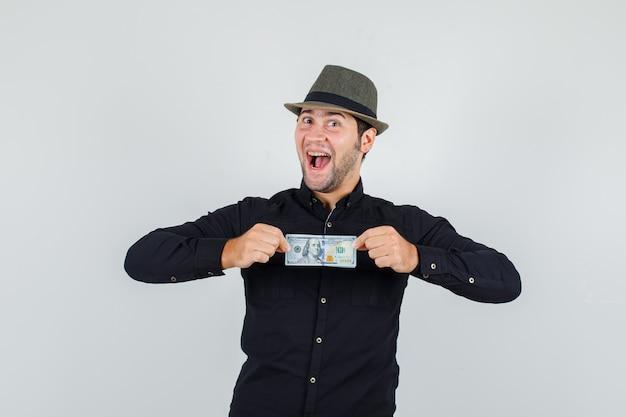 Joven sosteniendo billetes de un dólar en camisa negra, sombrero y mirando alegre