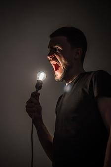 Un joven sosteniendo una bombilla encendida en la mano sobre fondo negro ideas conceptuales