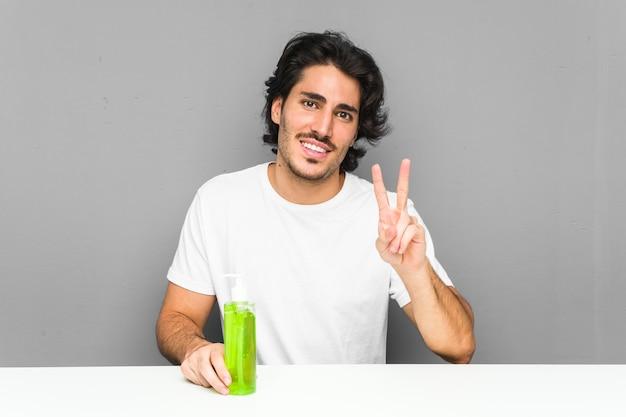 Joven sosteniendo una botella de aloe vera mostrando el número dos con los dedos.