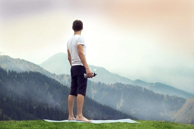 Joven sosteniendo una botella de plástico en la cumbre rocosa. concepto de entrenamiento de naturaleza pura.
