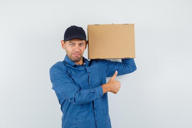 Joven sosteniendo una caja de cartón con el pulgar hacia arriba en camisa azul, gorra y mirando contento. vista frontal.