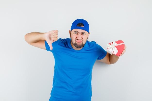 Joven sosteniendo caja de regalo con el pulgar hacia abajo en camiseta azul y gorra y mirando melancólico