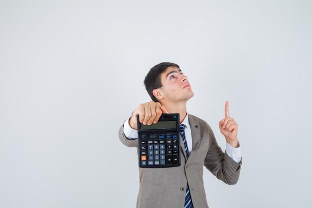 Joven sosteniendo la calculadora, apuntando hacia arriba con el dedo índice en traje formal y mirando enfocado, vista frontal.