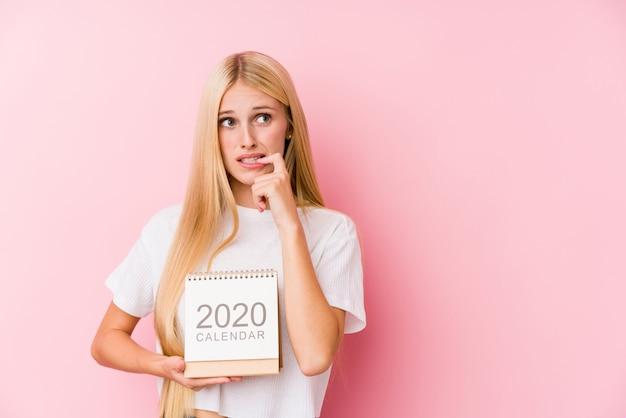 Joven sosteniendo un calendario 2020 relajado pensando en algo mirando un espacio de copia.