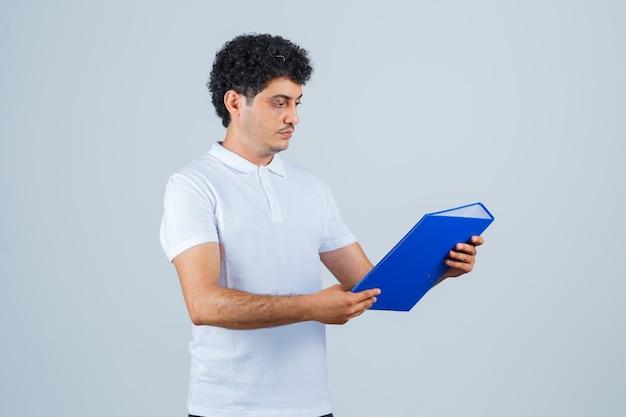 Joven sosteniendo la carpeta de archivos y mirándola en camiseta blanca y jeans y mirando enfocado, vista frontal.