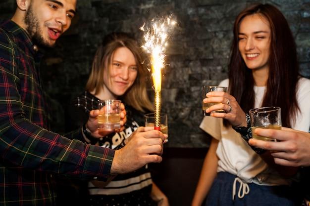 Joven sosteniendo chispa encendida celebrando con amigos