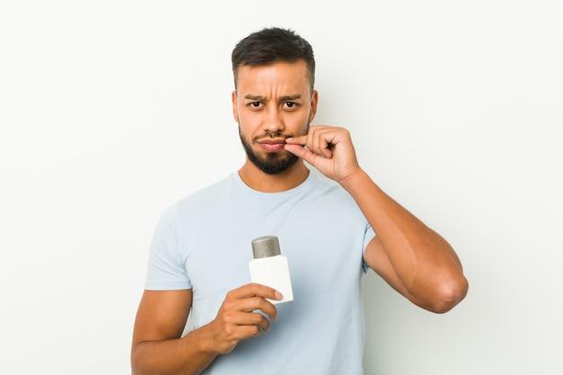 Joven sosteniendo una crema para después del afeitado con los dedos en los labios manteniendo un secreto
