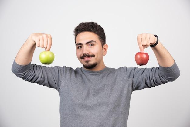 Joven sosteniendo dos manzanas en gris.