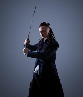Joven sosteniendo una espada samurai. foto de glamour.