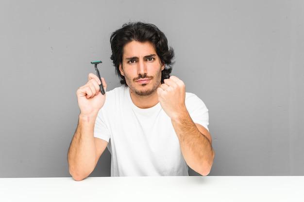 Joven sosteniendo una hoja de afeitar mostrando puño con agresiva expresión facial.