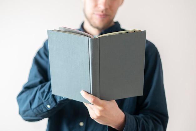 Un joven sosteniendo un libro, leyendo y obteniendo conocimientos de pie cerca de la pared, aislado