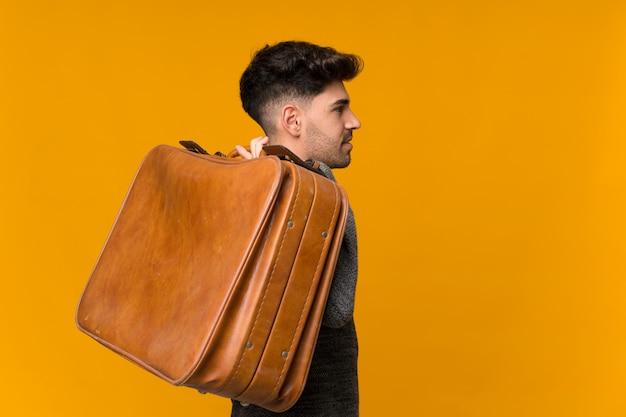 Joven sosteniendo un maletín vintage