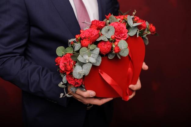 Joven sosteniendo en una mano una caja roja de rosas