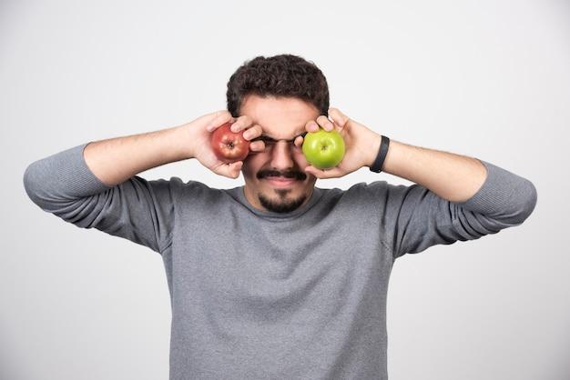 Joven sosteniendo manzanas verdes y rojas.