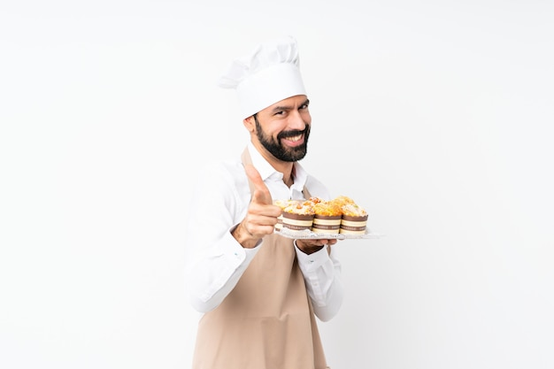 Joven sosteniendo pastel de muffin sobre aislado apuntando hacia el frente y sonriendo