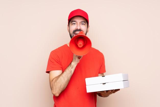 Joven sosteniendo una pizza sobre gritos aislados a través de un megáfono