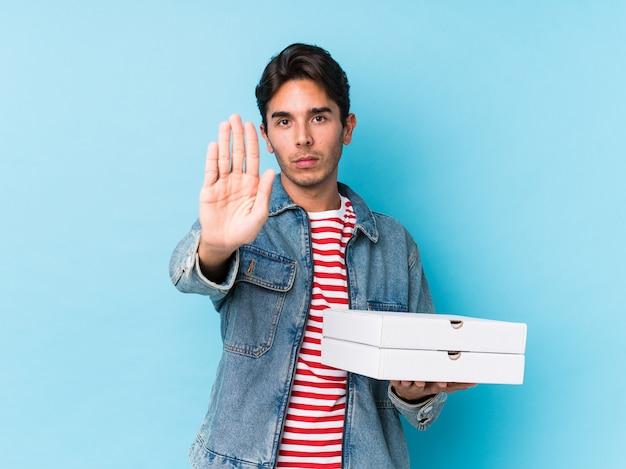 Joven sosteniendo pizzas aisladas de pie con la mano extendida que muestra la señal de stop, evitando que