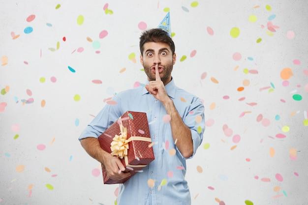 Joven sosteniendo presente rodeado de confeti