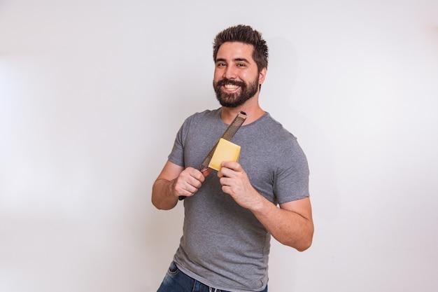 Joven sosteniendo un rallador y un trozo de queso en la mano sobre fondo gris. el hombre rallará el queso