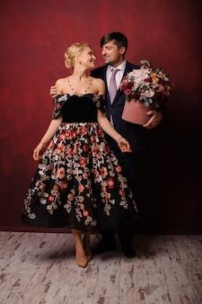 Joven sosteniendo un ramo de flores abrazando a su mujer