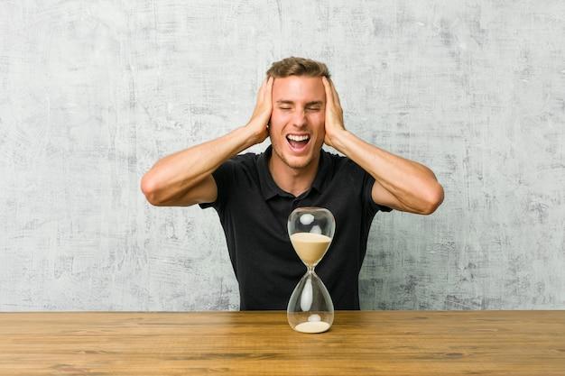 Joven sosteniendo un reloj de arena en una mesa ríe alegremente manteniendo las manos sobre la cabeza. concepto de felicidad