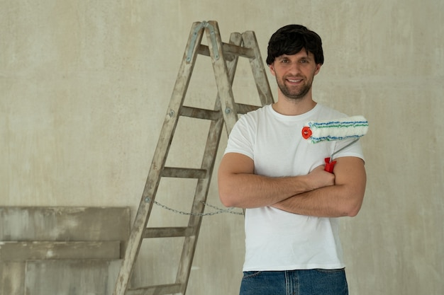 Joven sosteniendo un rodillo contra la escalera. pintor de casas hace reparaciones en casa