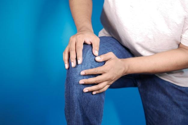 Joven sosteniendo su rodilla por sufrir dolor en las articulaciones contra el fondo azul.