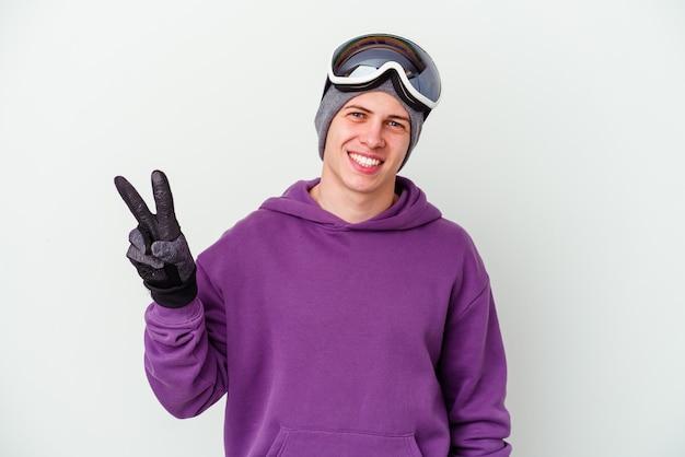 Joven sosteniendo una tabla de snowboard en blanco alegre y despreocupado mostrando un símbolo de paz con los dedos.