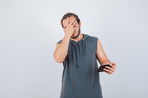 Joven sosteniendo el teléfono en la mano, cubriendo la cara con la mano en una camiseta con capucha y mirando infeliz, vista frontal.