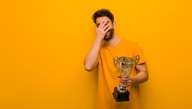 Joven sosteniendo un trofeo avergonzado y riendo al mismo tiempo