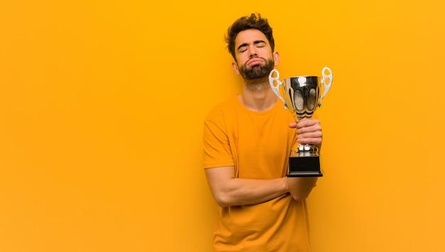 Joven sosteniendo un trofeo cansado y aburrido