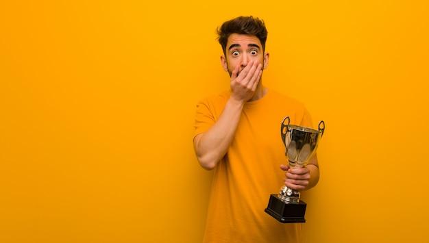 Joven sosteniendo un trofeo muy asustado y con miedo escondido