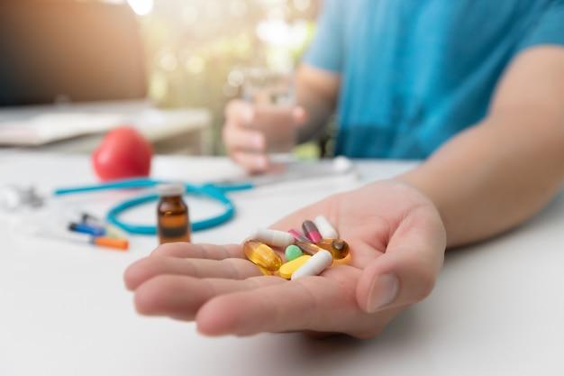 Joven sosteniendo una variedad de píldoras de medicina farmacéutica