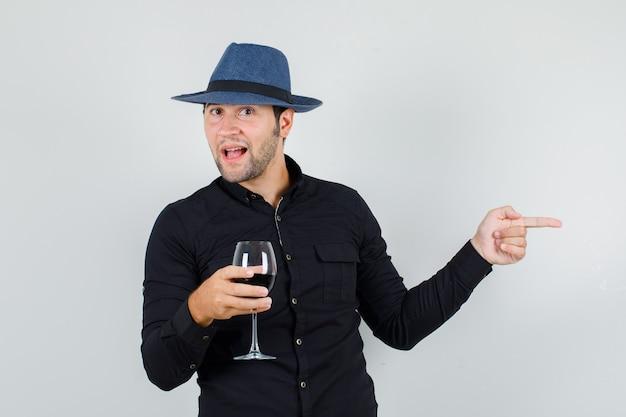 Joven sosteniendo el vaso de alcohol mientras apunta hacia un lado en camisa negra