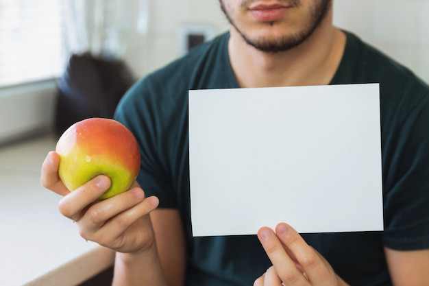 Un joven sostiene un cartel pidiendo ayuda. él no quiere comer alimentos saludables.