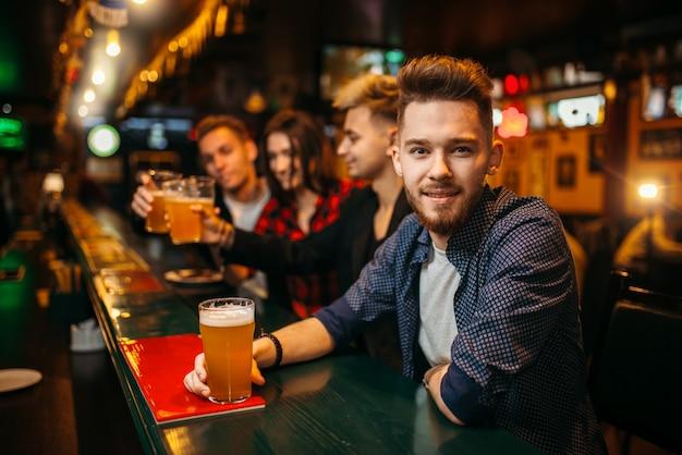 Joven sostiene un vaso con cerveza en la barra del bar en un pub deportivo, felices fanáticos del fútbol en el fondo