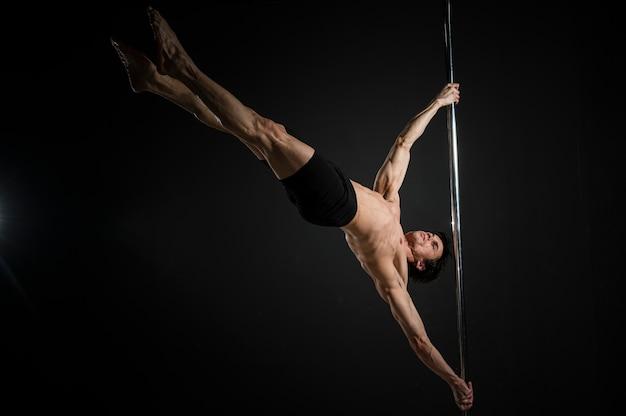 Joven stripper haciendo un pole dance