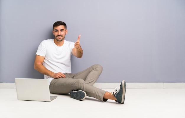 Joven con su computadora portátil sentado en el apretón de manos del piso después de un buen trato