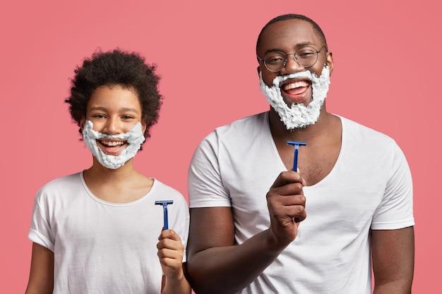 Joven y su hijo con espuma de afeitar en la cara y sosteniendo navajas