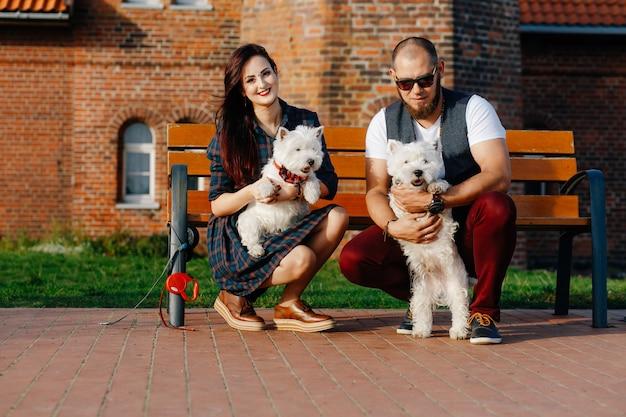 Una joven con su novio en cuclillas sosteniendo dos pequeños cachorros blancos