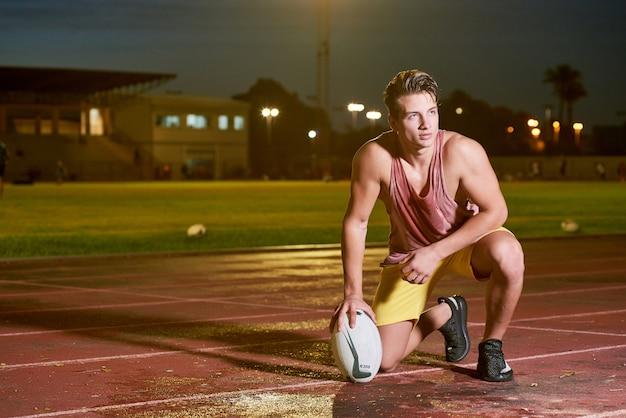 Joven sudor jugador de fútbol americano posando con una pelota en el estadio
