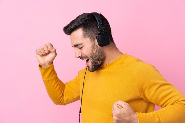 Joven en suéter amarillo bailando y escuchando música con auriculares