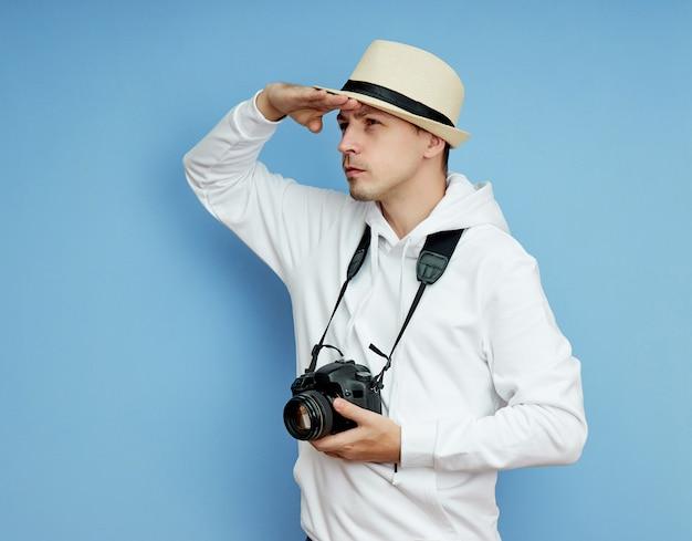 Joven en un suéter blanco con un sombrero y una cámara