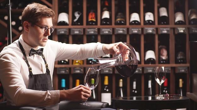 Joven sumiller vierte vino de una jarra en una copa de vino. primer plano del proceso de cata de vinos