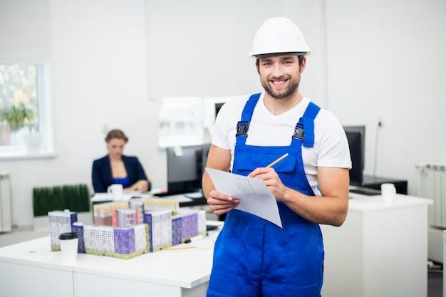 Un joven supervisor de construcción con un casco blanco y un mono azul tomando notas en la oficina