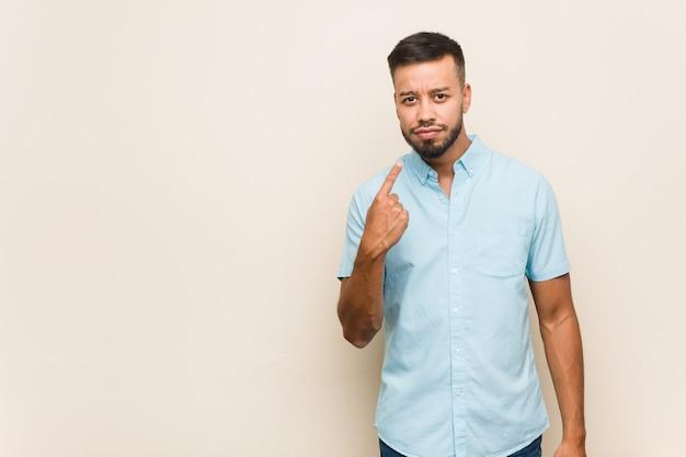 Joven surasiático apuntando con el dedo hacia ti como si invitara a acercarse.