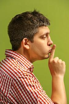 El joven susurrando un secreto detrás de su mano sobre la pared verde.
